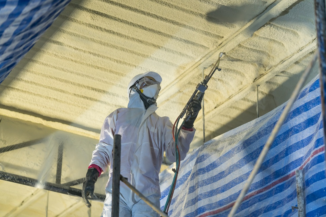 Technician sprays foam insulation to the inside of a roof